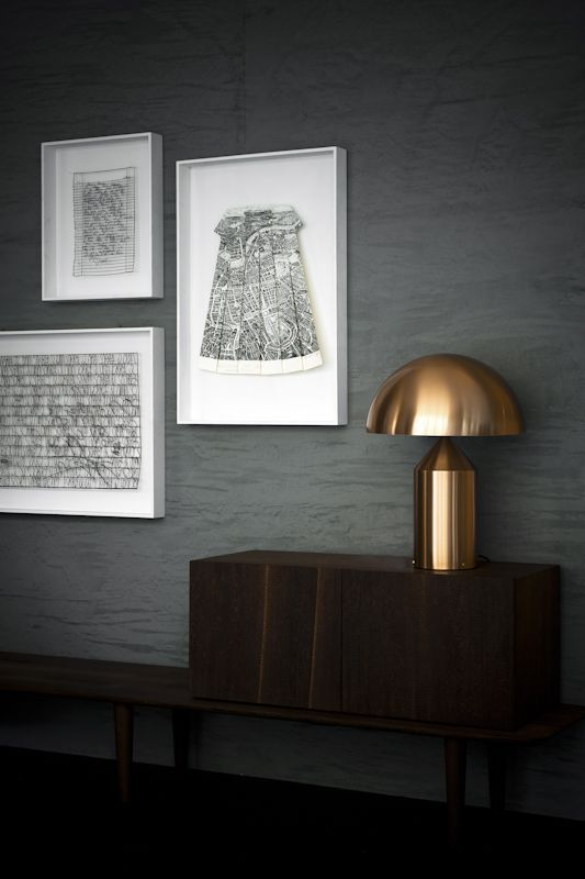 The satin gold finish of the Atollo-238 truly stands out against dark, black walls.