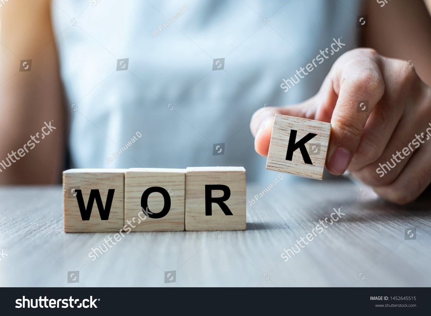 hand holding wooden cube block with WORK business word on table background hard Work and Life balance concept Businesswoman hand holding wooden cube block with WORK busin...
