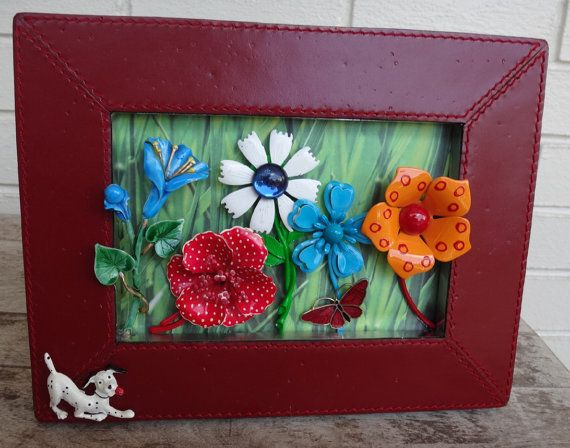 This little dalmation dog is keeping close eyes on his flowers! Vintage enamel flowers are in a distressed red leather frame with brushed