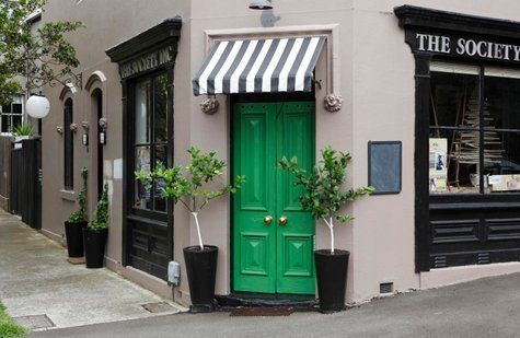 loving the kelly green door and striped awning!