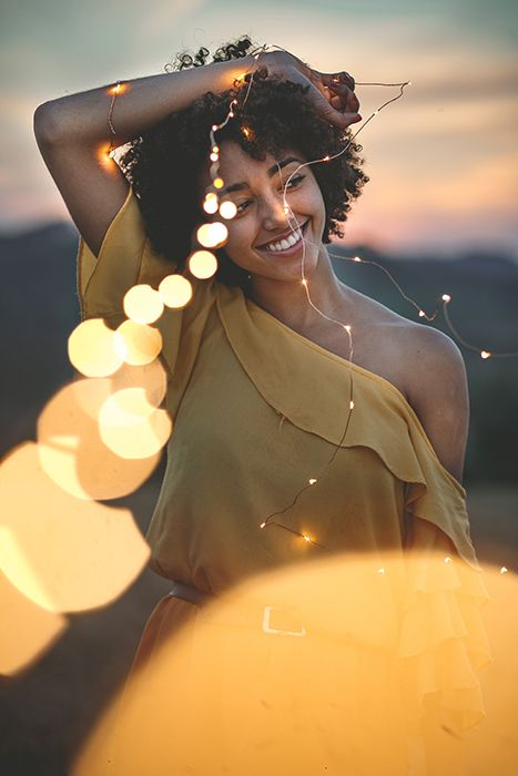 A creative outdoor portrait of a female model holding a string of lights - fairy light photography