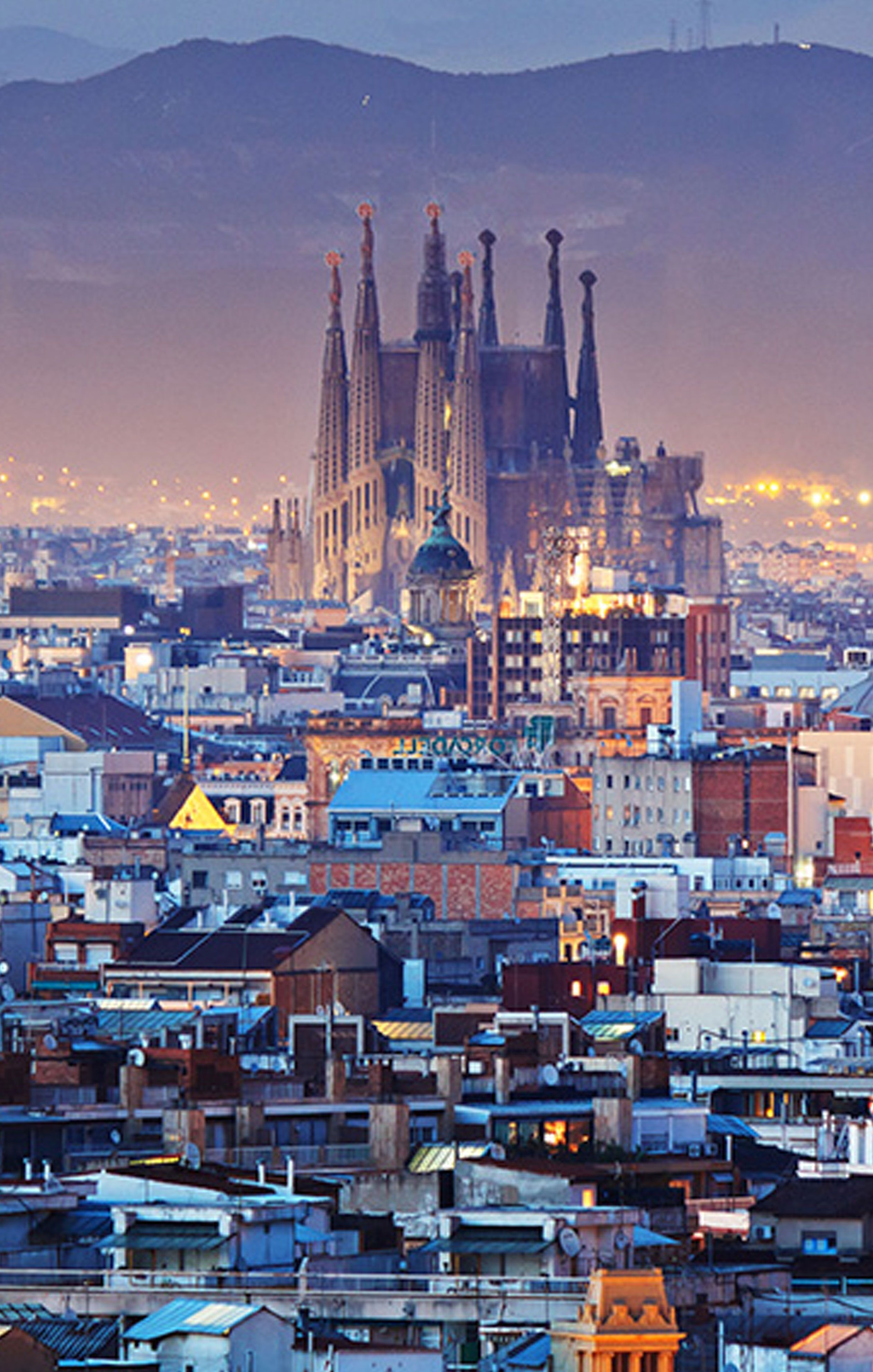 The skyline of barcelona lit up at night with gaudi 39 s la for Barcelona famila