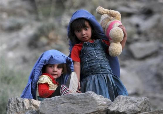 Afghan girls wear burqas for fun as they play near their house in Kabul July 21, 2011.   REUTERS/Mohammad Ismail