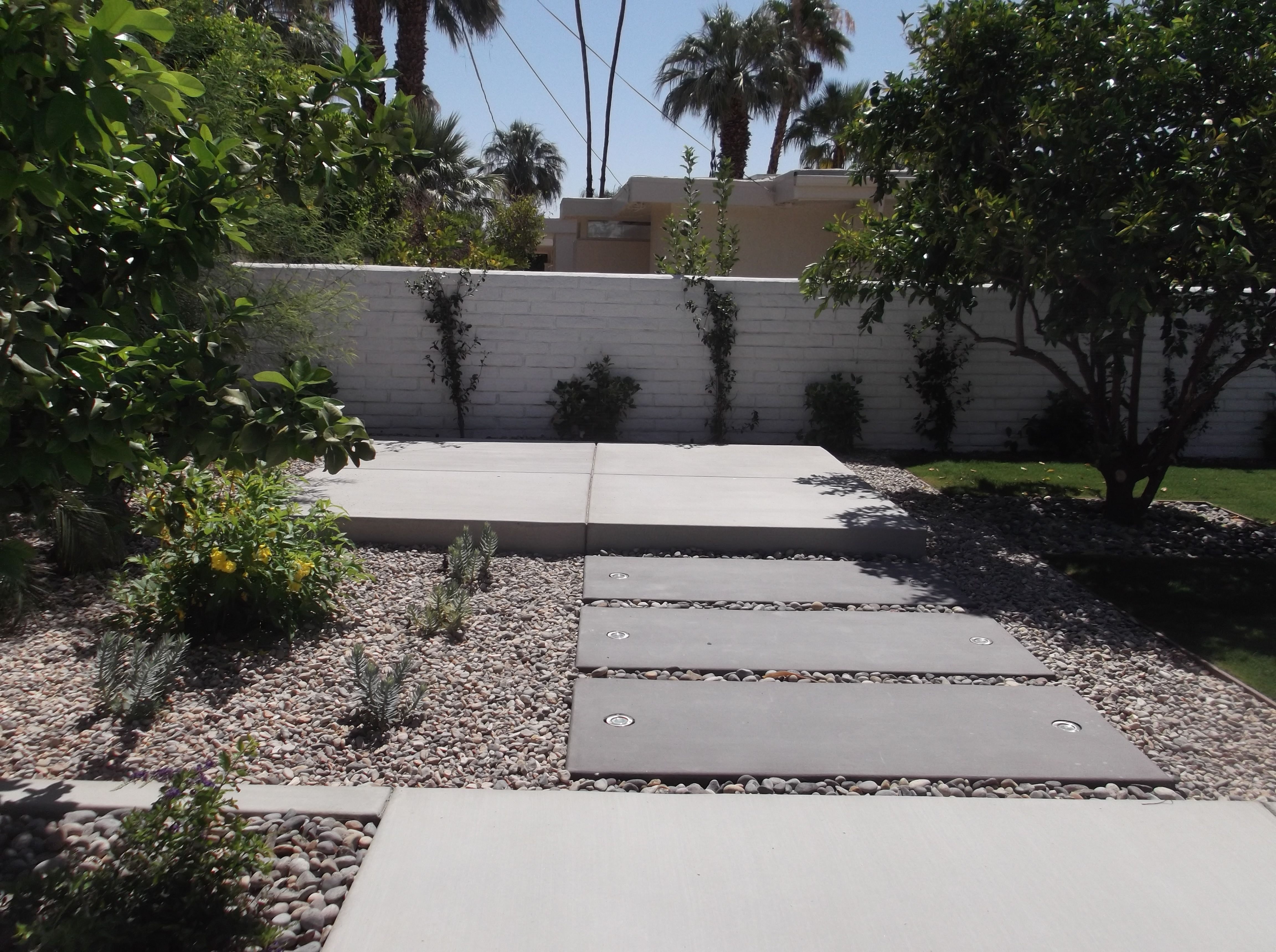 LED lights are embedded in this path that leads from the pool to a raised dining area nestled back between the citrus trees.