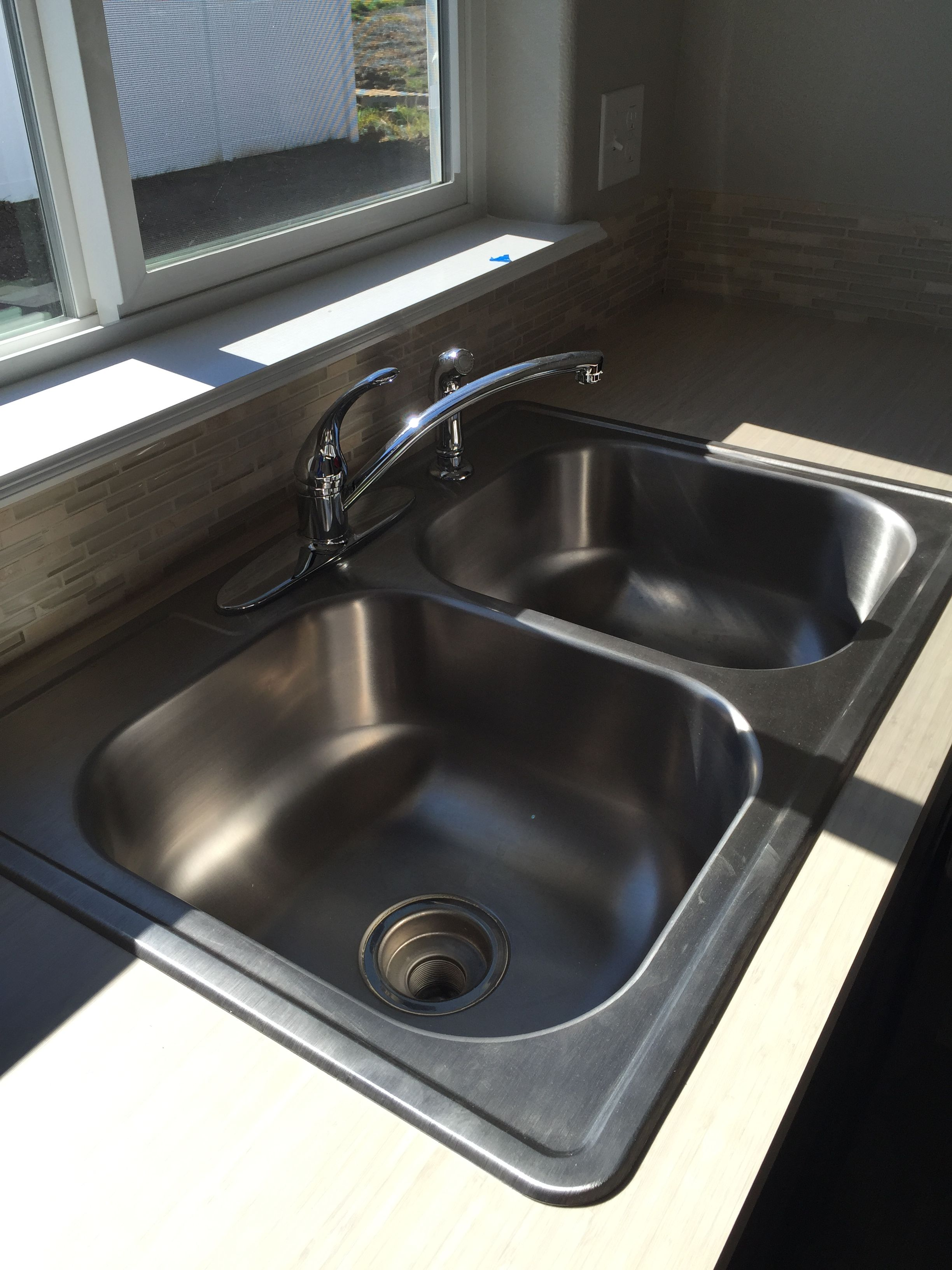 CBH Homes standard deep stainless steel sink with standard faucet for Legacy collection.