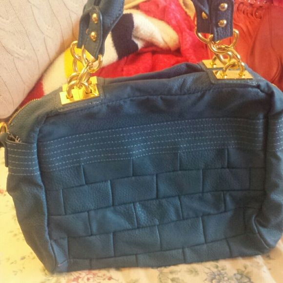 Blue handbag with gold hardware Unique designed purse with short handles with gold hardware. Perfect condition on the exterior, but interior has some minor stains, as pictured, from my bronzer exploding in the bag. Bags