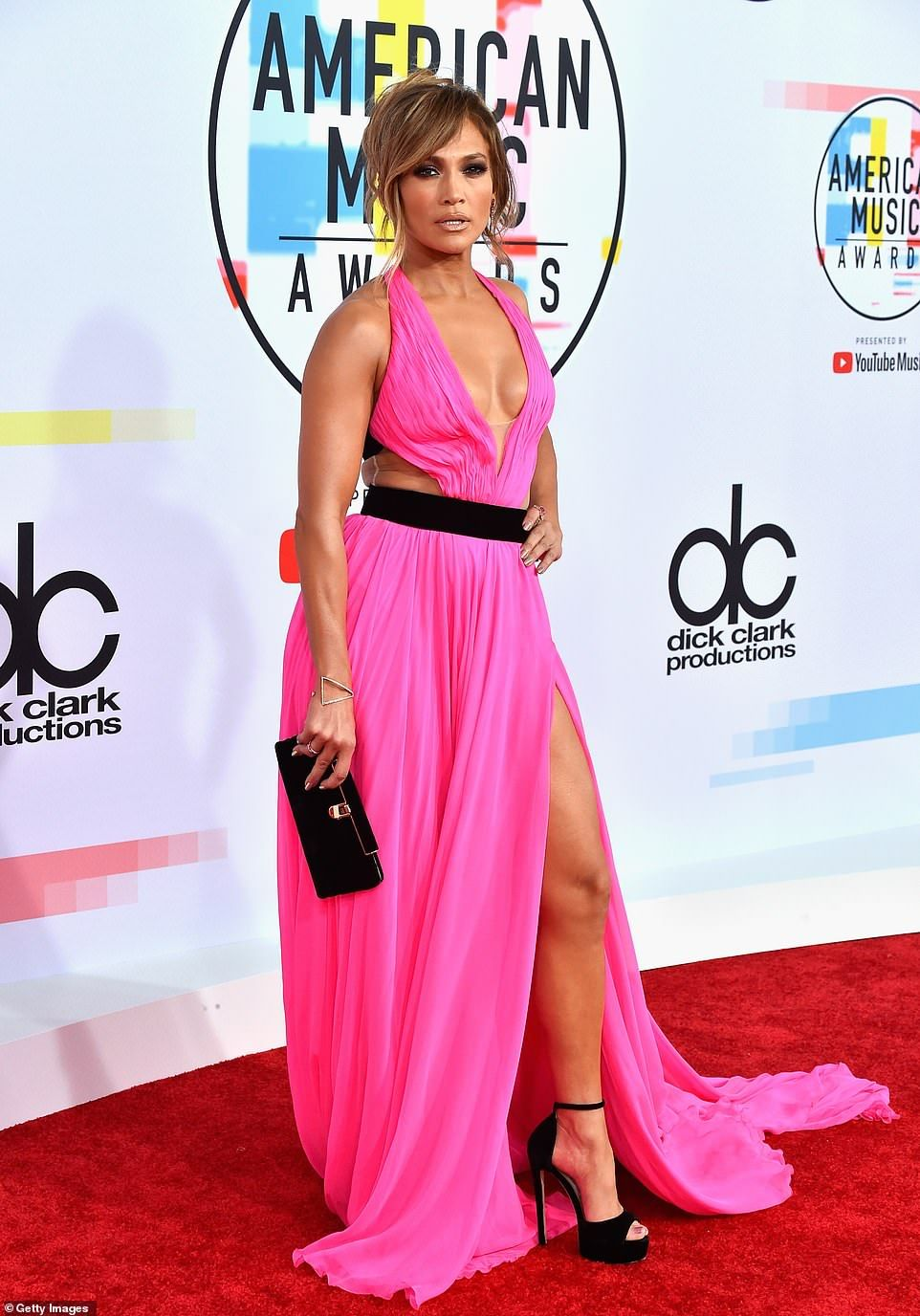 b736e404ca3c Iconic  Jennifer Lopez was sizzling in a hot pink Georges Chakra gown with plunging  neckline and thigh-high slit