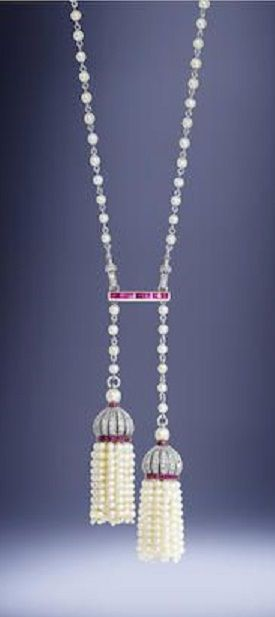 A Belle Époque pearl, ruby and diamond lavallière, by Andrey, probably for Cartier, circa 1910. The natural pearl and platinum chain connected by a calibré-cut ruby spacer via rose-cut diamond clasp mechanisms, suspending two seed pearl tassels of unequal length, each with a pierced cupola surmount millegrain-set with rose-cut diamonds and calibré-cut rubies, mounted in platinum and gold, maker's mark GA flanking a spray of mistletoe, French assay marks.