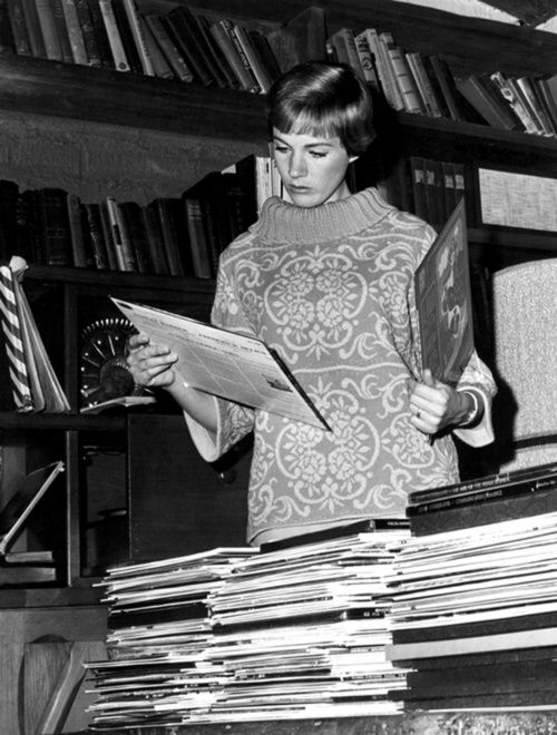 Julie Andrews looking through her record collection at her home in Hollywood, 1965