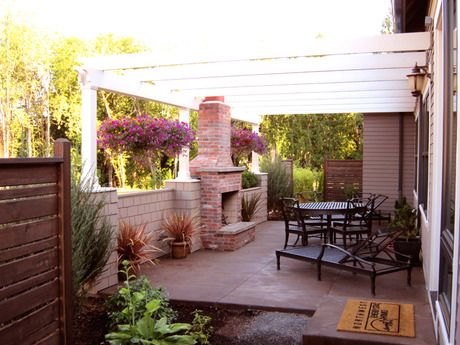 Attractive Hanging Plants Flank A Brick Outdoor Fireplace In This Tree Lined Private  Patio. New