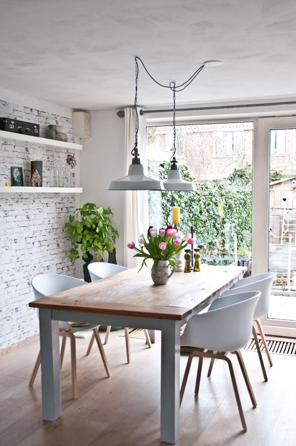 Modern Dining Room Decor Featuring An Exposed Brick Wall Painted White,  Open Shelves, White Side Chairs And Two Vintage Industrial Pendant Lights  Over The ...