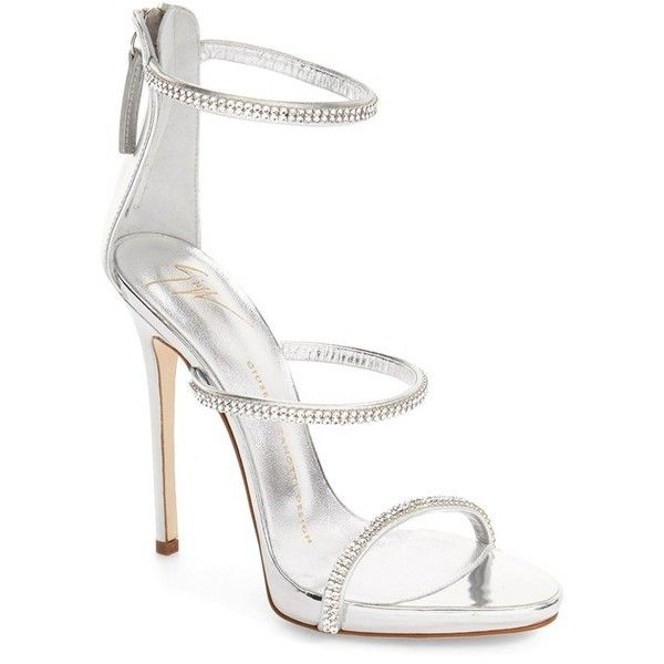 Crystals sparkle along the thin leather straps of a striking metallic sandal  lifted by a leg-lengthening tapered heel.Pre-order this style today!