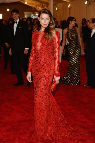 Amber Heard fit right in on the red carpet in a cherry red Emilio Pucci custom Chantilly lace gown with a matching studded minaudière, Pomellato jewels, and Casadei heels