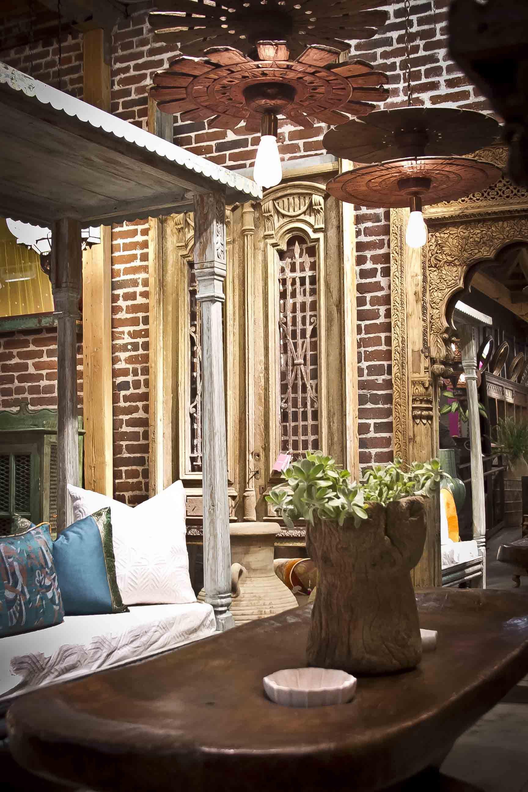 Antique Naga grinder table; rustic spindle chakra lights; vintage canopy day bed; antique Egyptian door; Jarokha arched antique mirror; old grain planters! www.de-cor.com