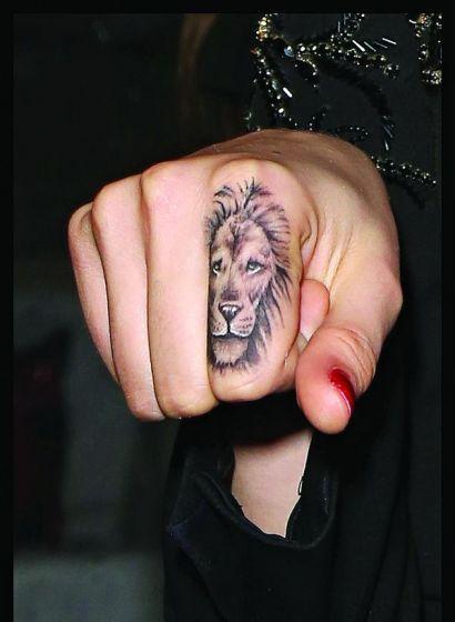 Cara delevingne estren tatuaje un le n en el dedo for Finger lion tattoo