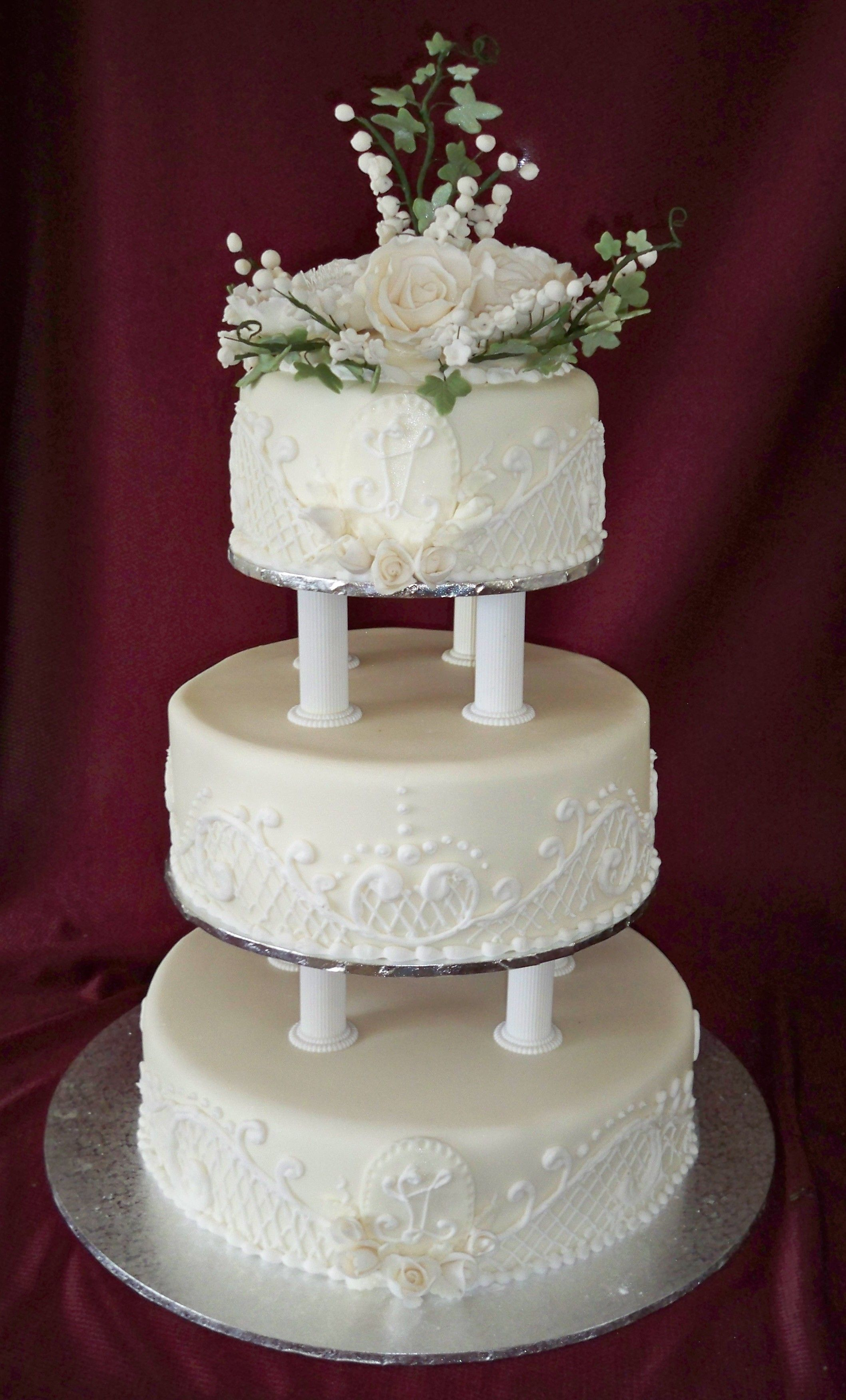 3 tier round wedding cake with 4 Roman columns supporting third