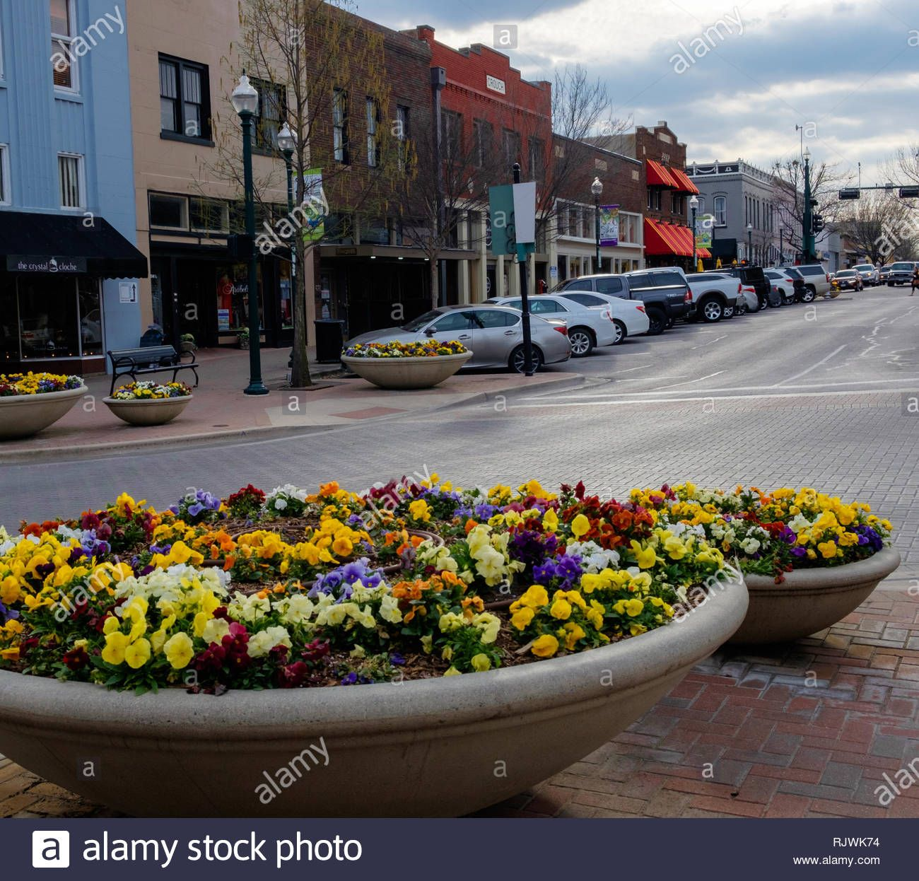 Colorful flowers in round cement planters decorate Main