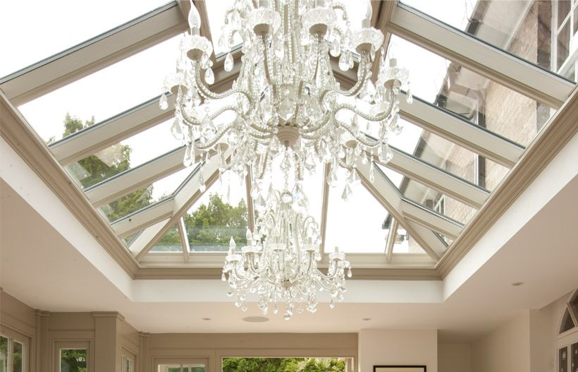 Stunning chandeliers hang from a contemporary orangery for Orangery lighting ideas