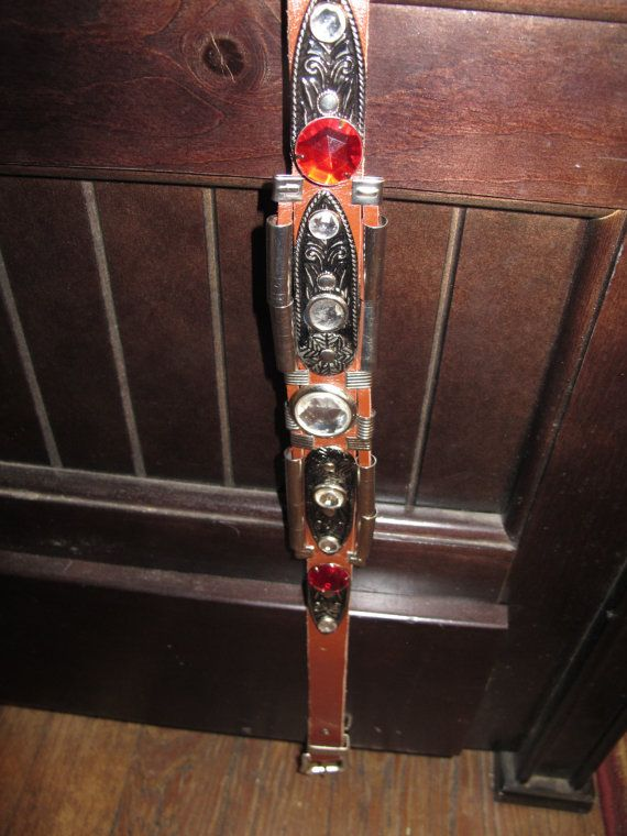 If you gotta have bling, you gotta have this belt! It is flashy and fun. It measures 35 inches long and the band is 1 inch wide, but it will be thicker in the back, where the metal embellishments and plastic rhinestones have been affixed to the leather band.  Yee haw