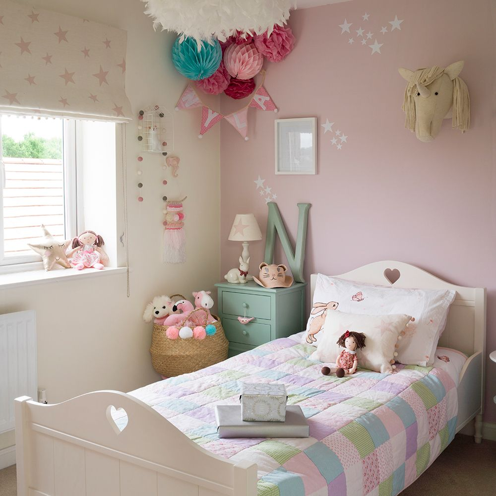 Girl's room in dusky pink with patchwork bed cover and pom