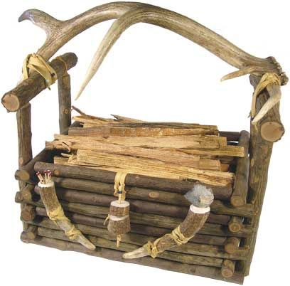 """HICKORY POLE BASKET - Hand wrapped hickory base and tines join the arched antler handle to a substantial pole basket. Ornamented on the front by two antler tines; one serves as a match holder, the other holds a piece of chipped stone to be used as a striker for lighting matches. 19""""L x 15""""W x 10""""D. Made in the USA!"""
