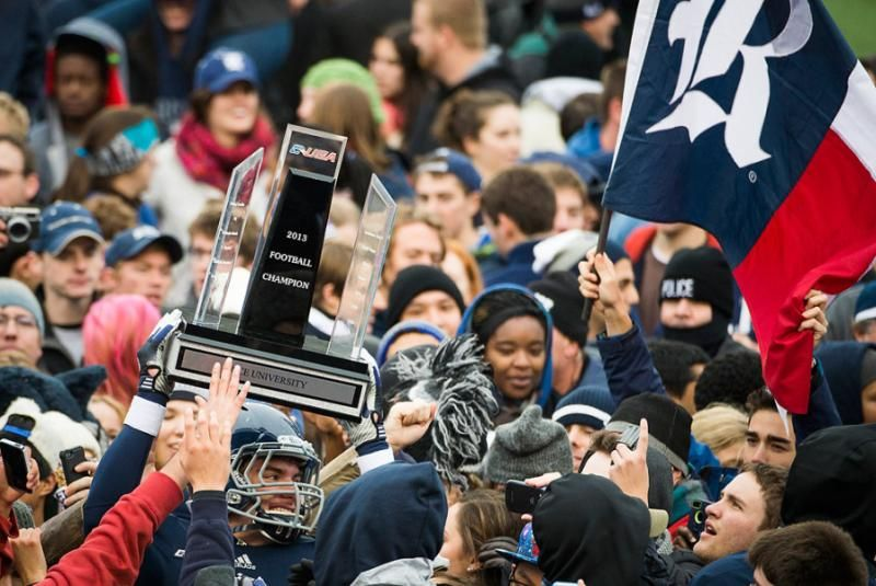 Rice fans storm the field and surround tight end Robby Wells III as he holds up the championship trophy after the Owls defeat Marshall 41-24 in the Conference USA title game in Houston. (Smiley N. Pool/Houston Chronicle)