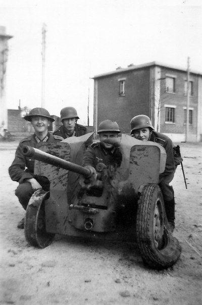 German soldiers posing next to the broken French 25-mm anti-tank gun Goccia (Canon antichar de 25 mm Hotchkiss Modele 1934).