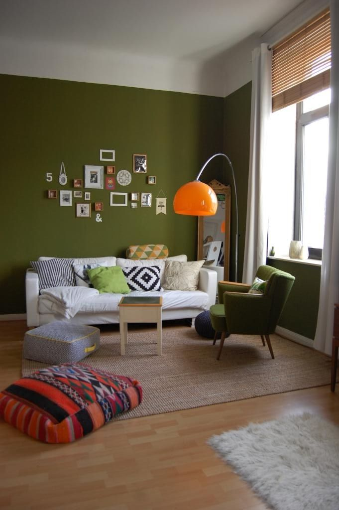Farbintensive Wohnzimmer-Inspiration dunkelgrüne Wand, orange Lampe