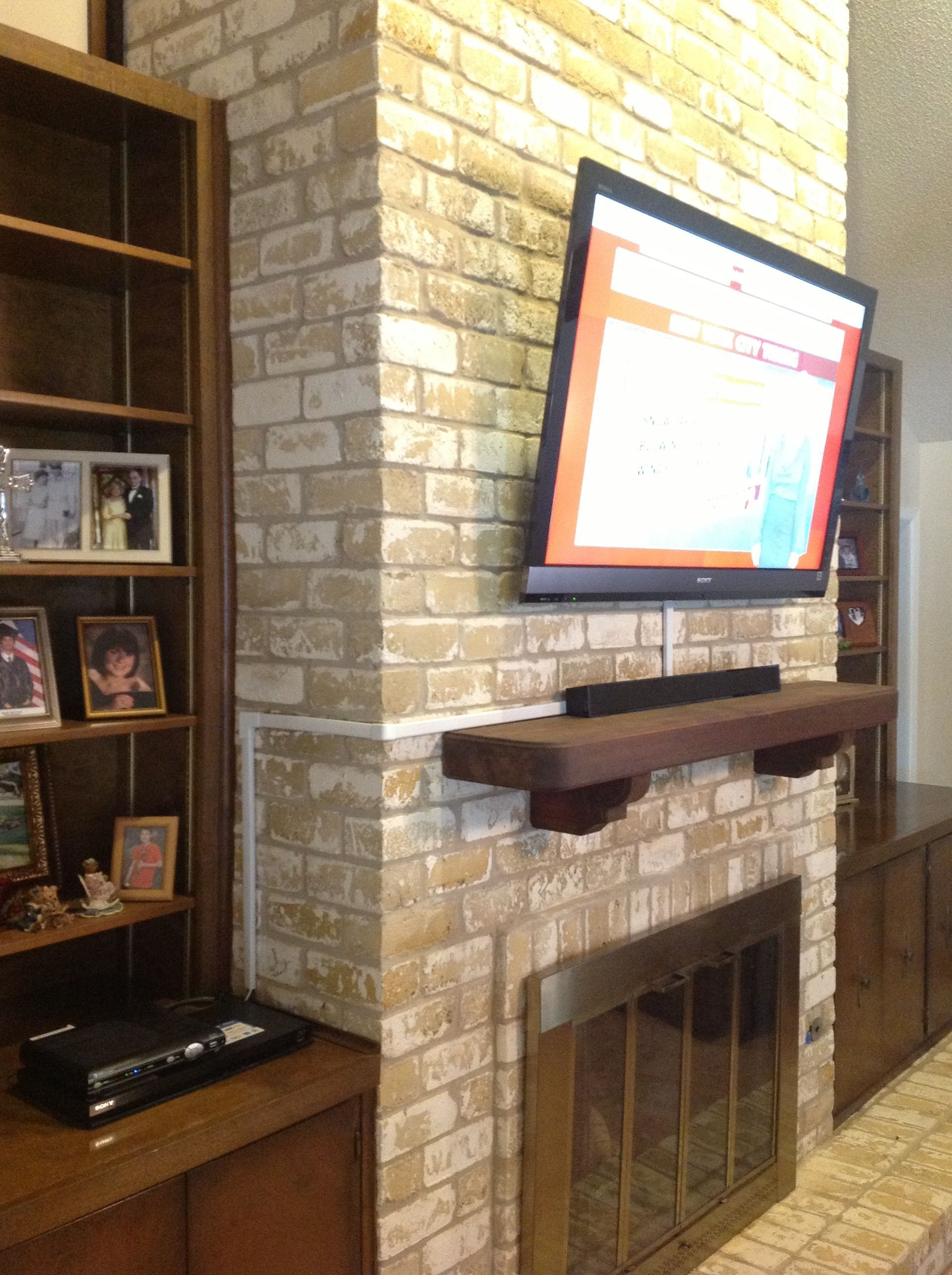 Tv wall mounting over a brick fireplace by ernesto
