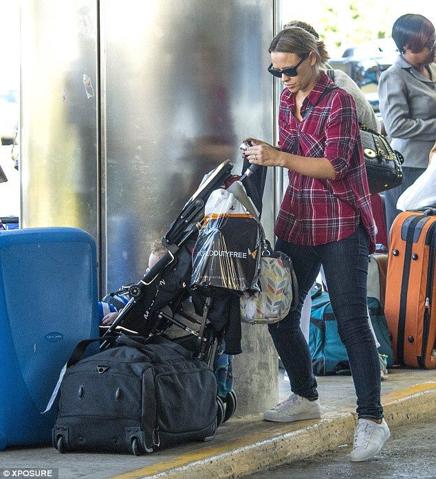 Low key look: She wore a checked shirt over blue jeans and trainers, wearing her hair in a...