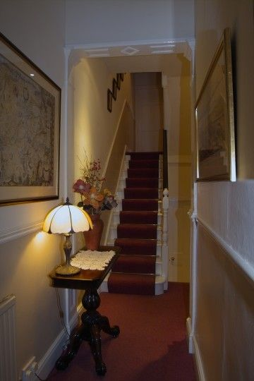 Traditional Edwardian Hall With Stair Carpet Runner And Brass Stair Rods.  Stairs And Spindles Painted White.