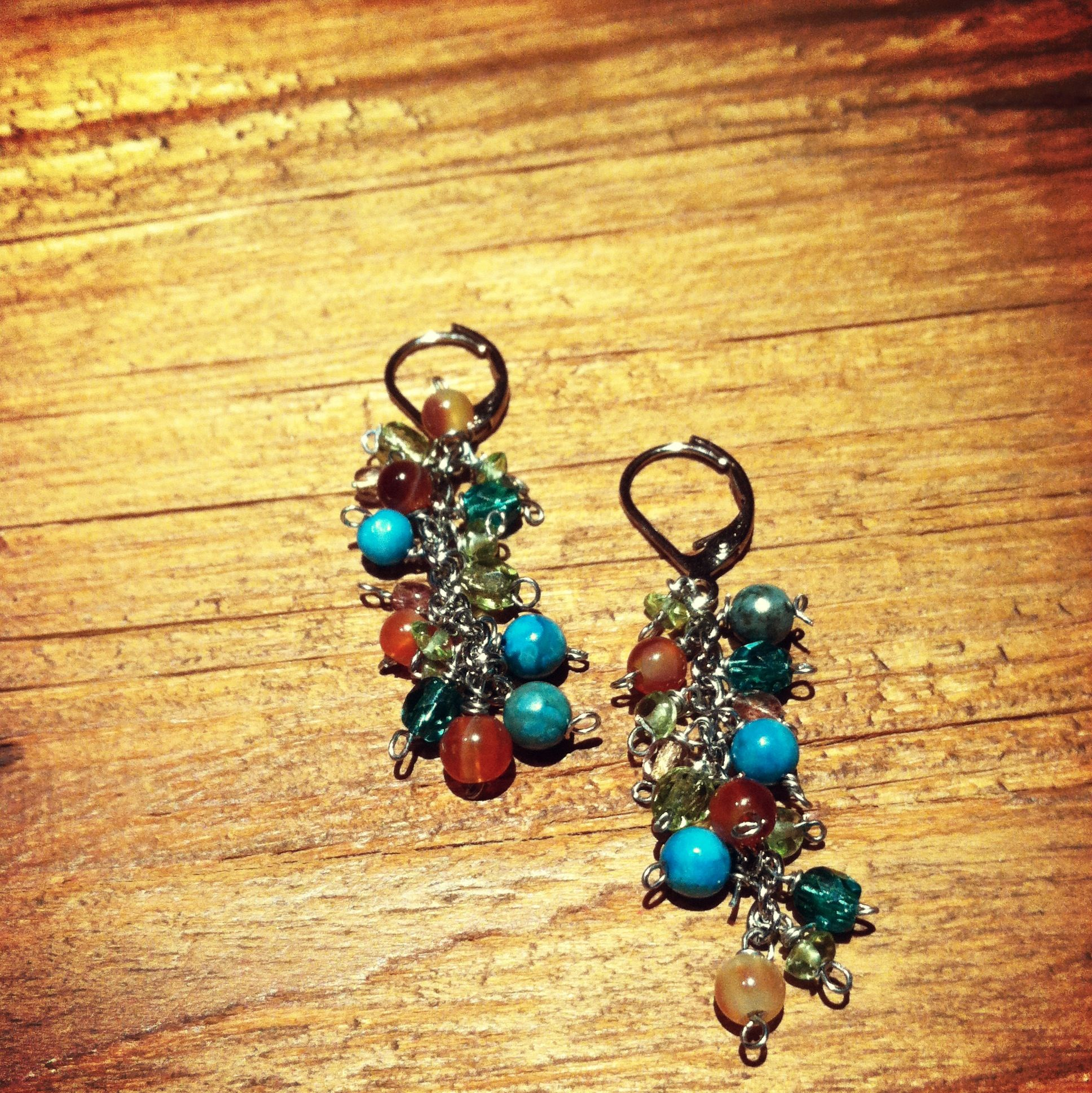 These earrings are a perfect fun accessory, they have turquoise, peridot, orange carnelian, teal crystal, green crystal,and bronze crystals. These will go with almost anything, the length is about 1-1/2 inches from the dangle.  $15.00