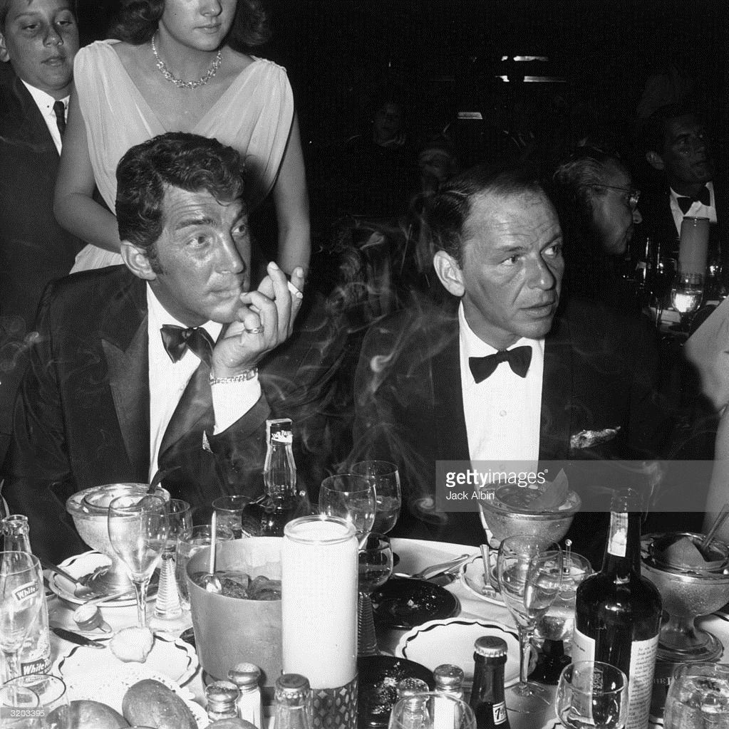American singers and actors Dean Martin (1917 - 1995) (L) and Frank Sinatra attend the opening night performance of American singer Eddie Fisher at the Cocoanut Grove, Hollywood, California. Martin and Sinatra are sitting around a dinner table covered with drinks and appetizers.