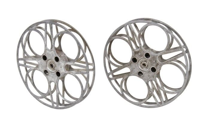 two matching vintage american oversized goldberg brothers cast aluminum filmstrip reels with highly stylized design
