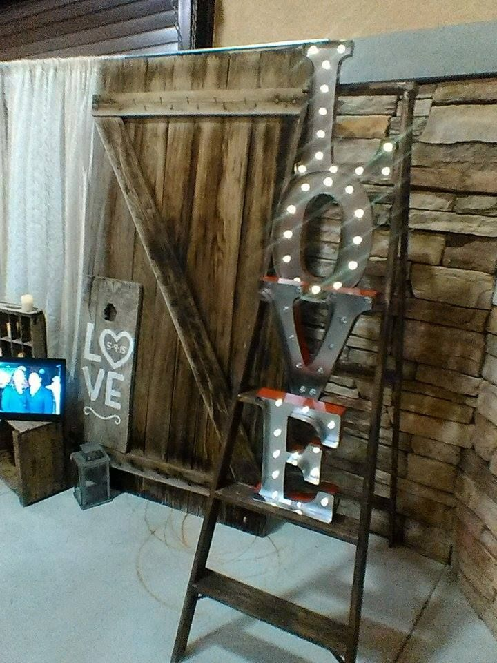 Marquee LOVE letters on a rustic ladder, barn door back drop.