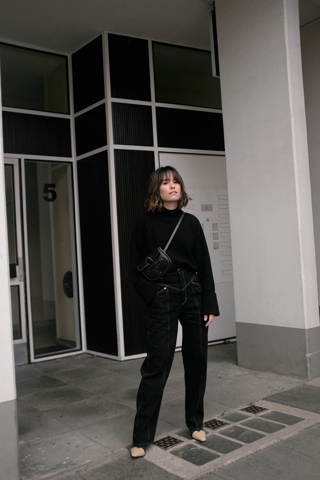 Nisi is wearing: Isabel Marant jeans, Céline Mini Symmetrical Bag, Céline  Madame boots, Black turtleneck knit
