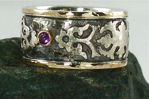 This Sterling Silver, 18k Gold inlay, and Amethyst ring is simply to die for! The ring is designed, crafted and completely hand engraved by the artist. After the 18k gold wire is inlaid in the boarder of the ring, and the settings are placed for the stones, the ring is oxidized (a process that turns silver black) to create an enhanced sense of depth and to accentuate the contrast of dark and light. Finally the exterior of the ring is polished to shine the high points of the piece and enhance…