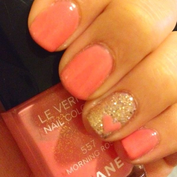 Coral nail polish with a gold accent nail and a coral heart