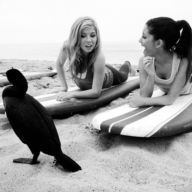 Candid picture of iCarly star Jennette McCurdy and Victorious star Ariana Grande laying on surfboards at the beach