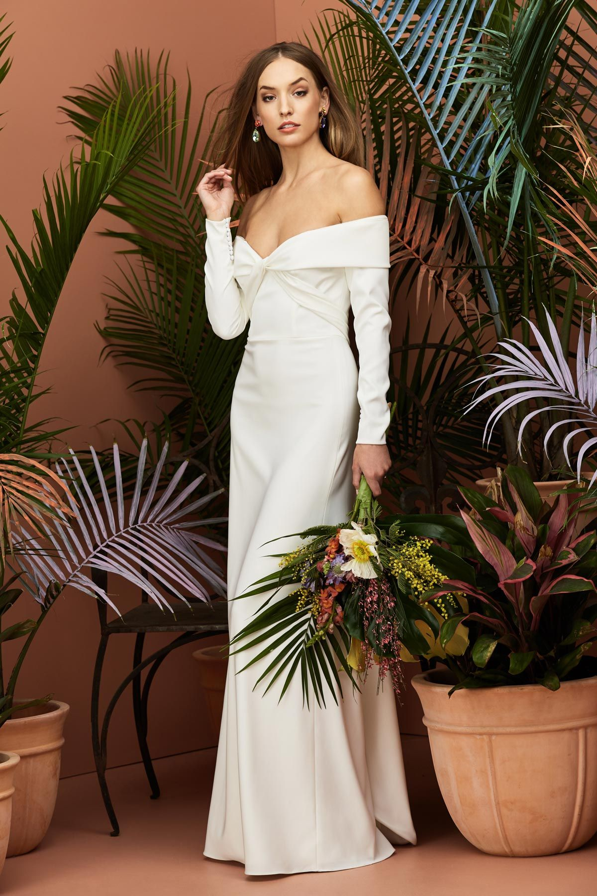 This wedding gown features a chic offtheshoulder style long