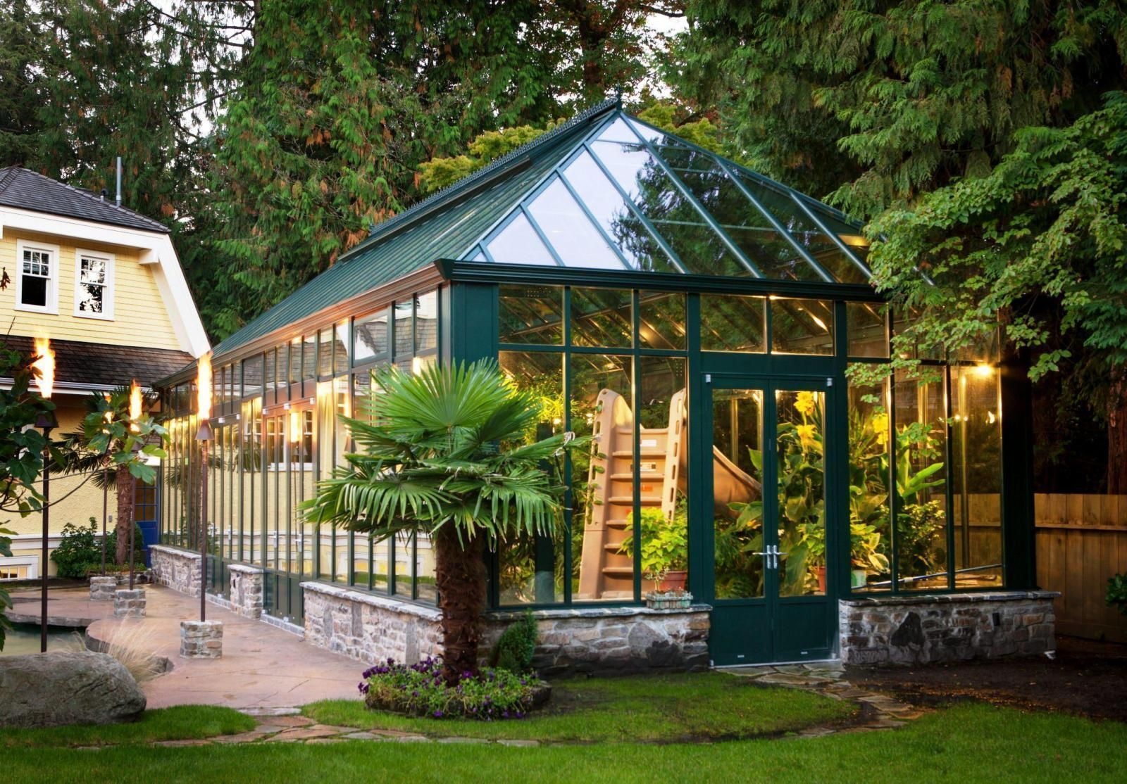 Green wooden framed home greenhouse designs with transparent glass