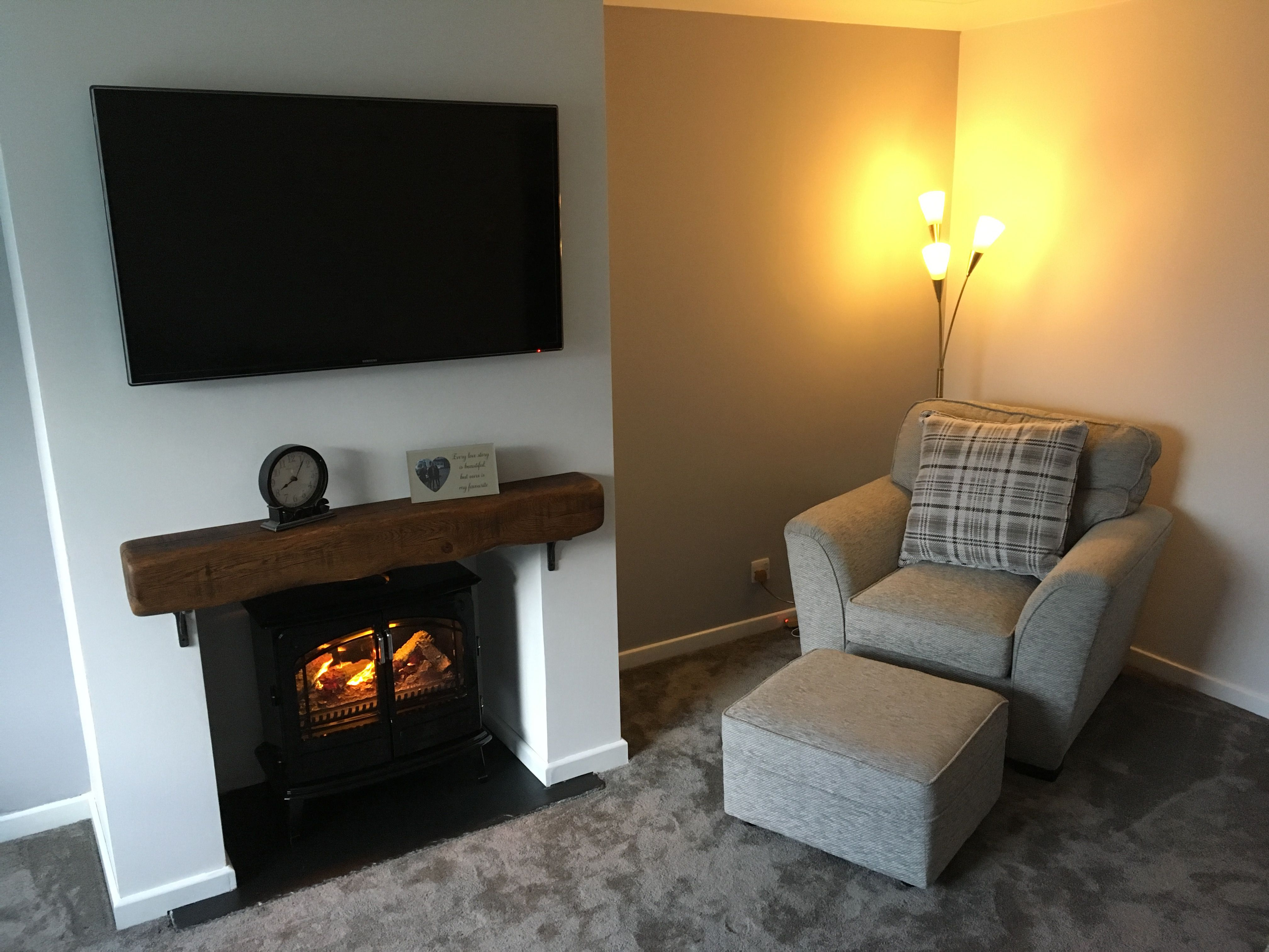 Grey living room with oak beam mantle fireplace with wall mounted TV
