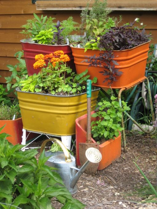 upcycled wash tubs dump find become herb planters outside kitchen...notice extra chimney flue bricks also painted and filled