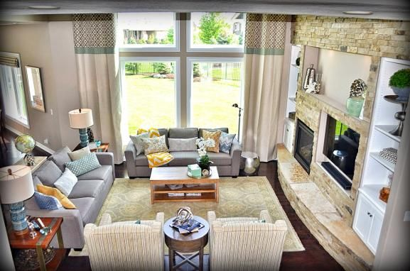 Two-story family room with stone fireplace, custom 15' drapes, pair of gray sofas in a soft grey and yellow color palette. Fluff Interior Design, Omaha, NE.