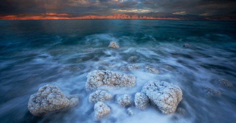 Pedras repletas de cristais de sal no Mar Morto, em Israel. A hipersalinidade do Mar Morto é fruto de sua geologia: inúmeros rios e córregos alimentam o lago fechado e os mineiras que são carregados até lá não têm para onde fluir Michael Melford/National Geographic Creative