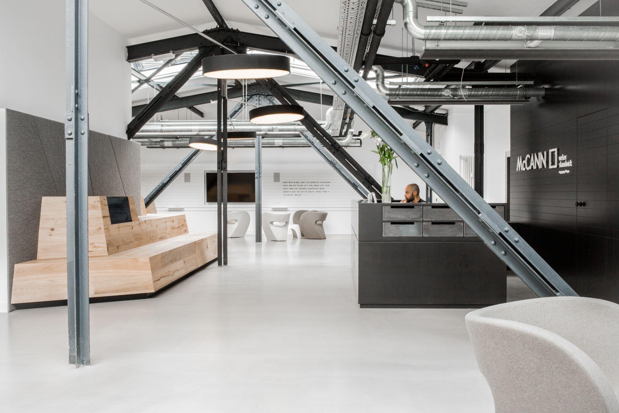 Empfangsbereich mit einer Sitztreppe aus Holz und im Kontrast dazu eine schwarze Theke