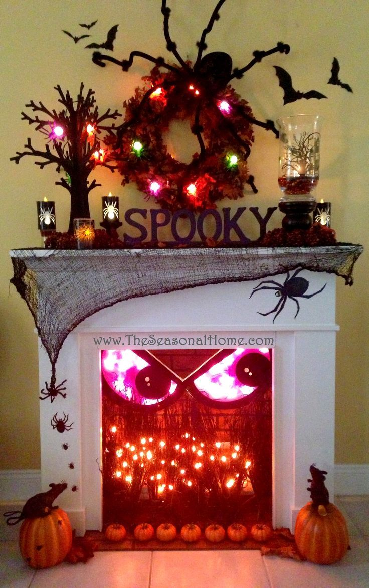 Halloween decorations face in the fireplace with spiders