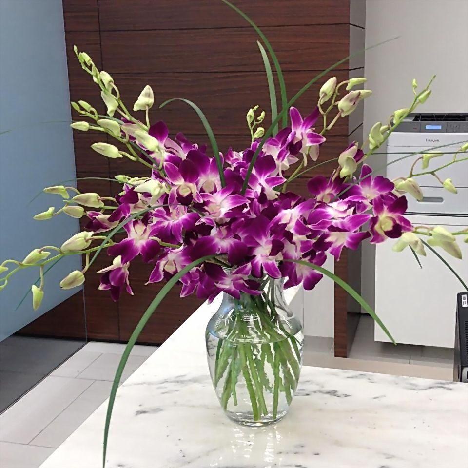 Stunning purple dendrobian orchid arrangement. Corporate florals, purple flowers, floral decorating ideas.