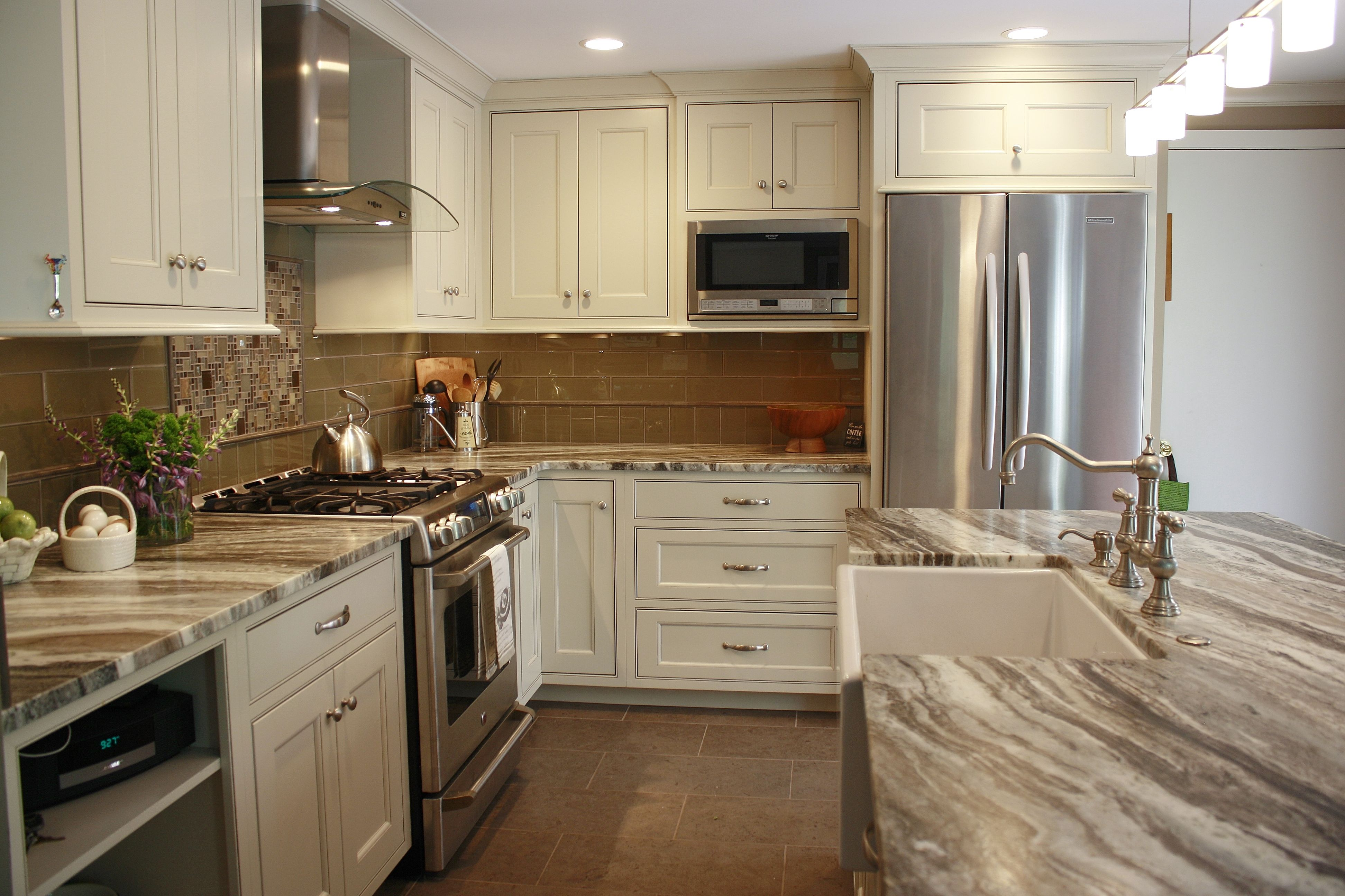This kitchen features brown fantasy leathered quartzite for White kitchen cabinets brown granite countertops