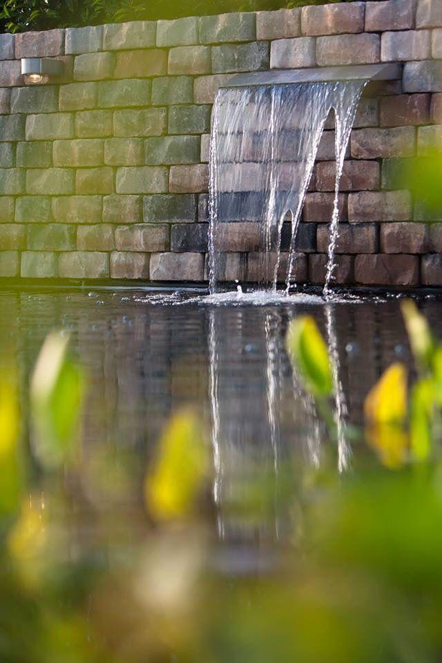 Waterspuwer brievenbus in muur van stapelblokken bij een for Zwemvijver benodigdheden